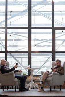 Gravi uomini d'affari di mezza età in abiti in stile retrò che bevono superalcolici mentre rispondono ai messaggi sui telefoni