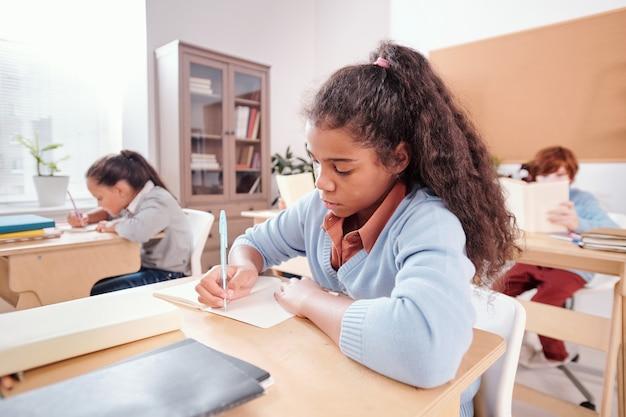 Studentessa seria di razza mista che prende appunti o scrive un saggio in un quaderno mentre è seduta alla scrivania a lezione e lavora individualmente