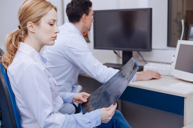 Grave oncologo femminile lunatico seduto sulla sua sedia e guardando le immagini a raggi x pur essendo insoddisfatto della diagnosi