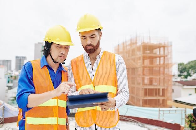 Appaltatore e costruttore multietnico serio che discute progetto o orario di lavoro sul computer tablet