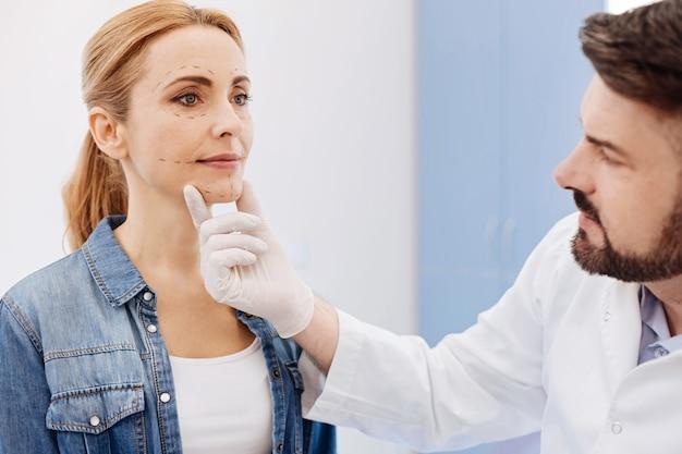 Serio simpatico chirurgo estetico che tiene il mento dei suoi pazienti e guarda il suo viso mentre la prepara a una chirurgia estetica del mento