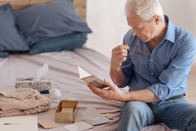 Uomo anziano bello serio che si mette gli occhiali e legge una vecchia cartolina pur avendo ricordi nostalgici