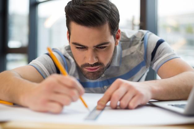 Uomo bello bello serio che tiene i suoi strumenti e che fa un disegno mentre lavorava come ingegnere