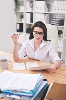 Responsabile di ufficio serio o analista in abiti da cerimonia che esamina documenti finanziari mentre è seduto alla scrivania con una pila di documenti intorno