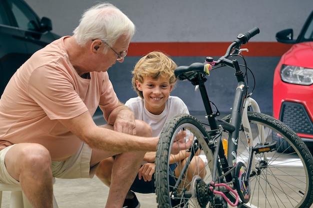 Uomo anziano serio che mostra il dettaglio del ragazzo della bicicletta