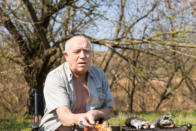 Grave vecchio seduto sulla sua sedia a rotelle arrostire salsicce di carne per il suo pranzo nell'area del campo in una giornata molto soleggiata