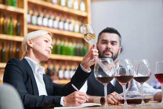 Sommelier professionisti seri esaminano il colore del vino bianco in bokal mentre uno di loro ne scrive le caratteristiche