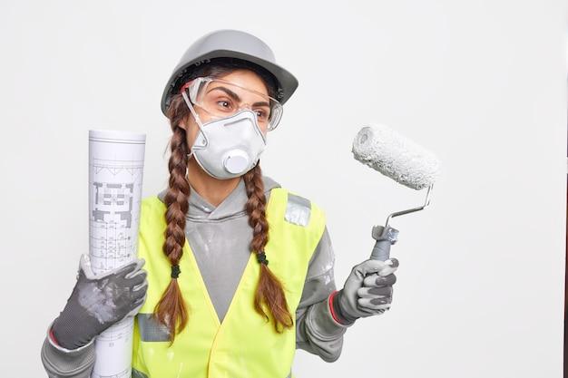 L'architetto professionista serio responsabile della stesura di piani dettagliati per la struttura e lo sviluppo della costruzione indossa guanti protettivi per il casco con maschera facciale e tiene il rullo di vernice del progetto