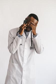 Medico afroamericano serio perplesso che parla sul telefono