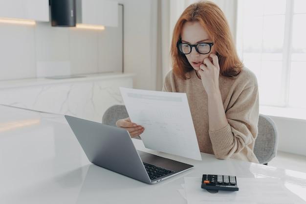 Una donna rossa seria focalizzata sui documenti cartacei usa la calcolatrice e il computer portatile