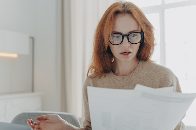 Una giovane donna rossa seria focalizzata su documenti cartacei studia il rapporto finanziario