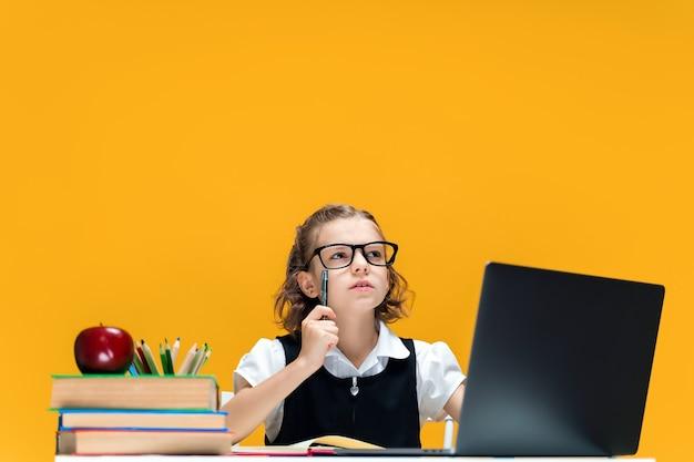Studentessa seria con gli occhiali che alza la penna seduta alla scrivania con l'istruzione a distanza del computer portatile