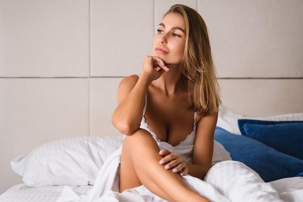 Donna seria seria svegliarsi e sedersi in un lussuoso letto bianco con gamba nuda e scollatura in reggiseno di pizzo, guardare la finestra durante la bella mattinata con la mano sul mento, godersi il momento.