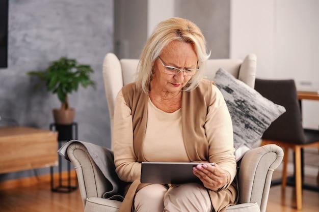 Donna anziana seria seduta sulla sua sedia a casa e che usa il tablet per cercare su internet i sintomi del virus corona.