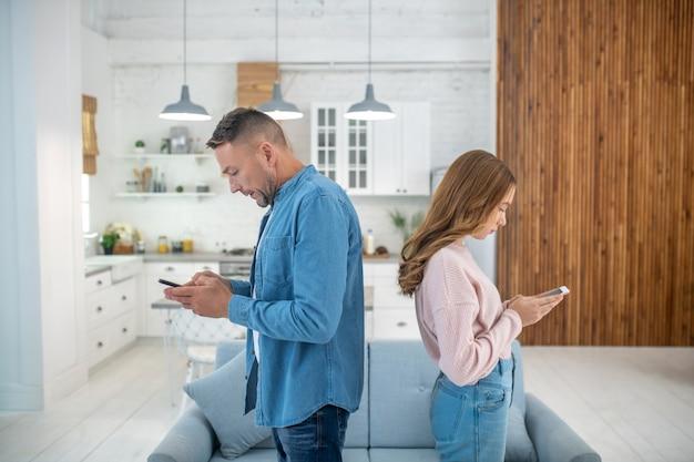 Padre e figlia seri e silenziosi in piedi schiena contro schiena, ognuno guardando il proprio smartphone.