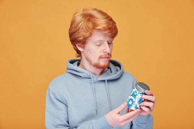 Giovane uomo dalla barba rossa scettico serio in felpa con cappuccio che legge l'etichetta sulla bottiglia di vitamina sull'arancio