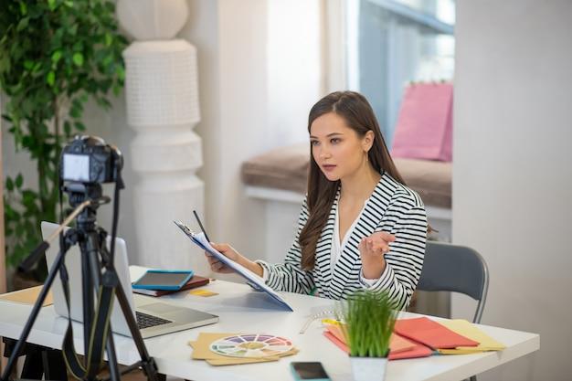 Una donna seria e intelligente che dà consigli importanti durante lo streaming di video per il suo blog