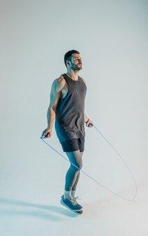 Sportivo serio che salta con la corda per saltare. il giovane uomo europeo barbuto indossa l'uniforme sportiva. isolato su sfondo turchese. riprese in studio