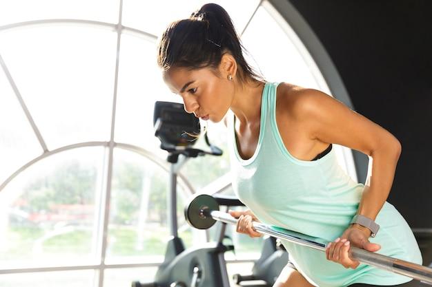 Sportiva seria facendo esercizio con bilanciere in palestra