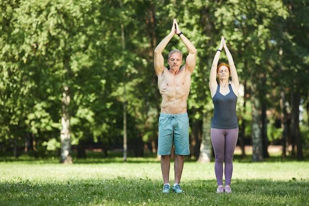 Coppia matura sportiva seria in piedi con le mani alzate in namaste e facendo esercizio di respiro nel parco estivo