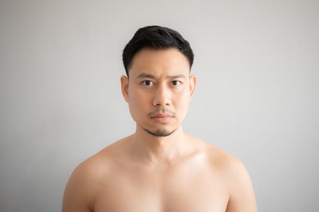 Fronte di sforzo e serio dell'uomo asiatico in ritratto topless isolato su sfondo grigio.