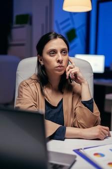 Donna d'affari stressata seria che ha una conversazione con un cliente. imprenditrice che lavora a tarda notte in azienda facendo gli straordinari nel corso di una telefonata.