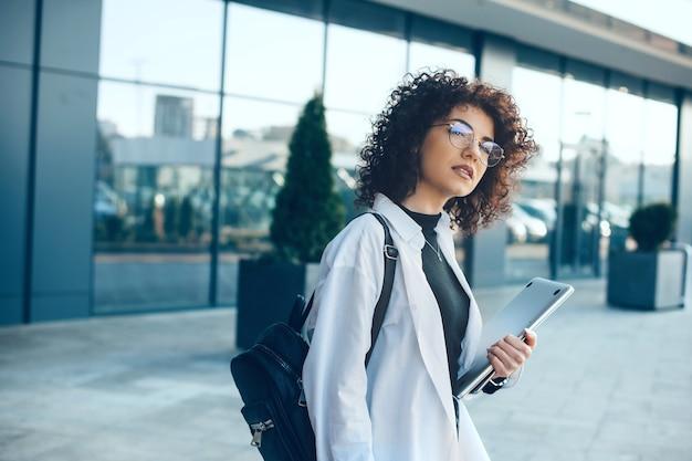 Studente serio con occhiali e capelli ricci è in posa mentre tiene un laptop e una borsa