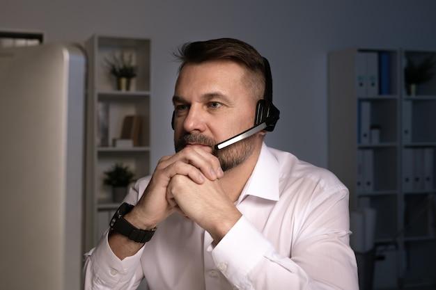 Operatore telefonico serio con auricolare guardando lo schermo del computer mentre consulta i clienti online dal posto di lavoro