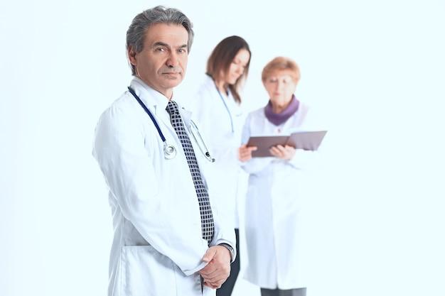Grave terapista medico su sfondo sfocato di colleghi.