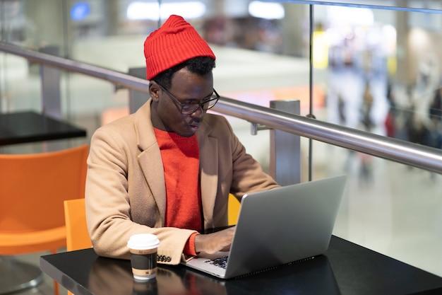 Uomo serio viaggiatore seduto al caffè in aeroporto lavora sul portatile in attesa di un imbarco