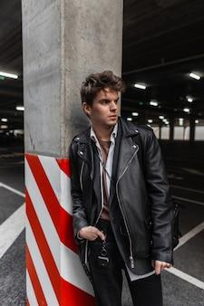 Modello serio alla moda giovane in una giacca di pelle nera alla moda oversize giovanile con un'acconciatura alla moda si trova vicino a una colonna grigia in un parcheggio cittadino. bel ragazzo moderno hipster in strada