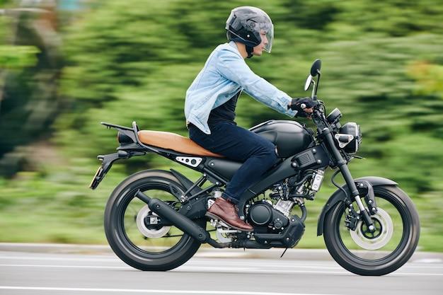 Uomo vietnamita serio che guida veloce sulla moto, cespugli sfocati