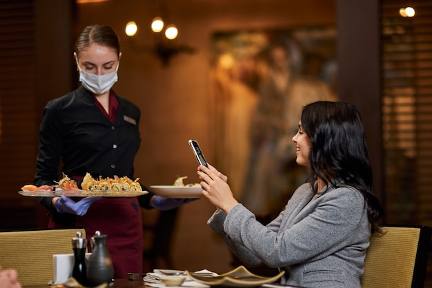 Cameriera seria in maschera protettiva che consegna l'ordine del cibo mentre la donna ne scatta una foto sul suo smartphone