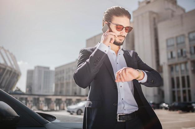 Giovane serio e ben vestito cammina per strada. parla al telefono e guarda gli orologi. guy è in fretta. lui è in ritardo.