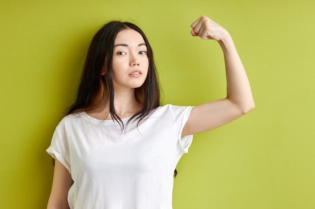Donna seria che mostra i muscoli forti isolati sopra priorità bassa verde, femmina potente del brunette in maglietta bianca casuale esamina la macchina fotografica