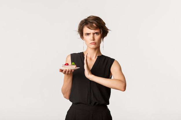 Donna seria sulla dieta rigorosa che rifiuta il pezzo di torta, mostrando il gesto di arresto, levandosi in piedi sopra il bianco.
