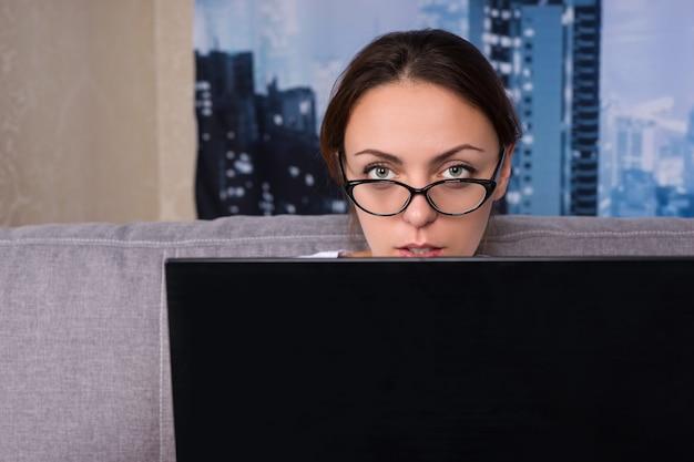 Donna seria con gli occhiali che sbircia dietro il laptop mentre lavora e fa i suoi affari a casa