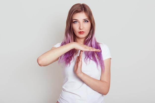 Donna seria con capelli lilla in maglietta casual bianca, mostrando il gesto di time out