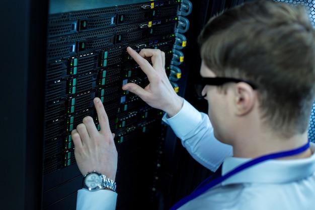 Lavoro serio. operatore concentrato esperto che lavora e premendo i pulsanti neri