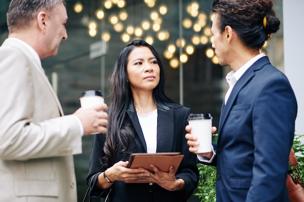 Signora seria giovane asiatica di affari con il computer della compressa che esamina i suoi colleghi parlanti quando sono in piedi all'aperto