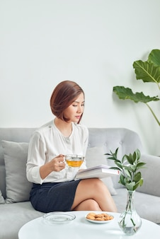 Grave giovane ragazza asiatica in camicetta e gonna seduto sul divano e bere il tè durante la lettura del libro in soggiorno