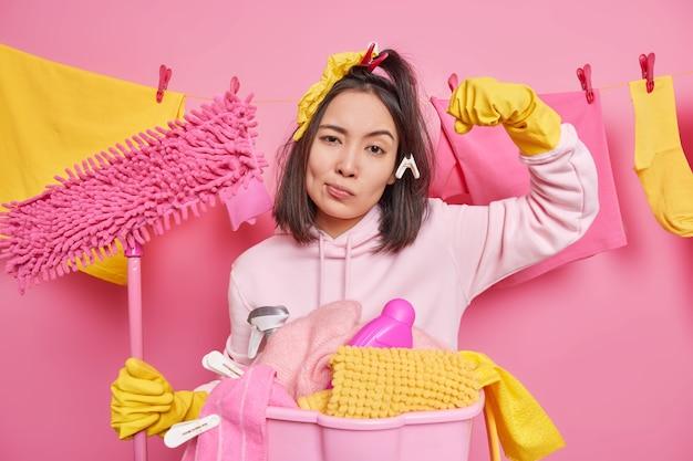 Una giovane donna asiatica seria alza il braccio e mostra i muscoli pronti per fare i lavori domestici