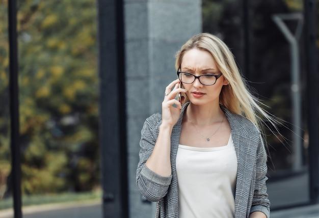 Grave giovane donna attraente per le imprese parlando al telefono sullo sfondo di un ufficio commerciale. cattive notizie