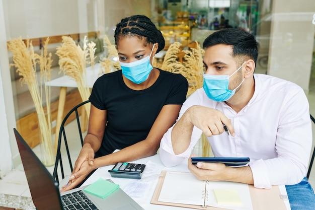 Gravi giovani proprietari di panifici in maschere mediche che discutono di rapporti finanziari dopo la bocca del lavoro durante una pandemia