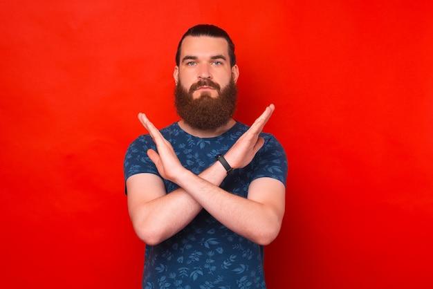 Il giovane uomo barbuto serio sta incrociando le mani per lo stop o il segnale sufficiente.