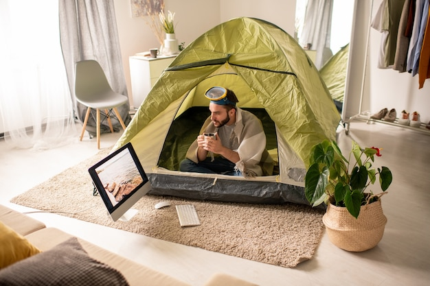 Grave giovane uomo barbuto con maschera subacquea sulla testa seduto in tenda a casa e bere il tè mentre guarda la foto del mare sullo schermo del computer