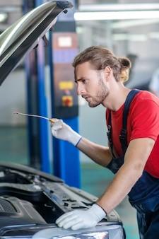 Grave giovane uomo barbuto con dispositivo speciale in mano in piedi sotto il cofano aperto dell'auto