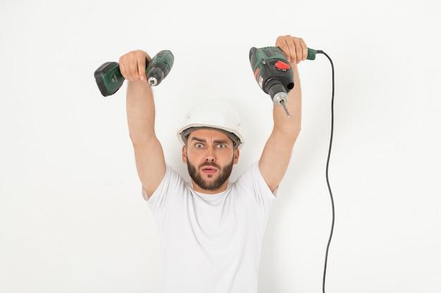 Grave giovane riparatore barbuto in elmetto protettivo che tiene utensili manuali mentre si prepara per il rimodellamento in appartamento