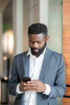 Grave giovane imprenditore nero in tuta in piedi nel corridoio e utilizza lo smartphone mentre manda un sms con i colleghi