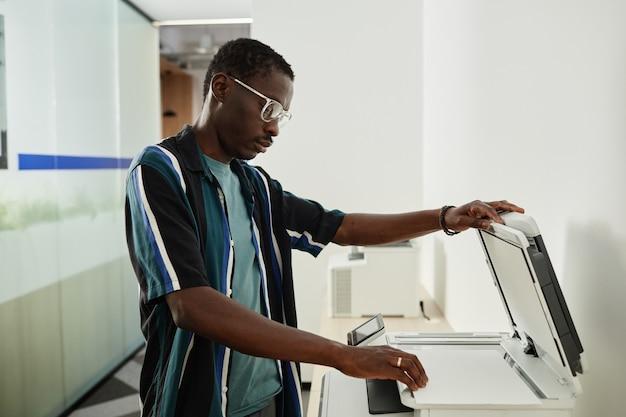 Giovane uomo di colore serio che usa una fotocopiatrice per fare copie del contratto per l'incontro